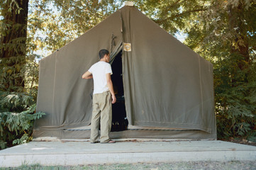 Rear view of man peeking into tent