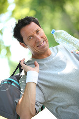 Sporty looking man drinking from a large bottle of water