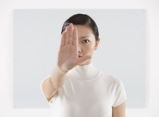 Portrait of woman with hand in front of face
