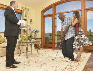 Couple playing golf in house with servant watching