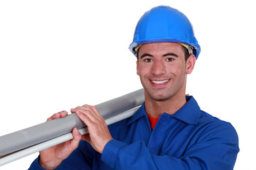 A construction worker carrying a long tube.