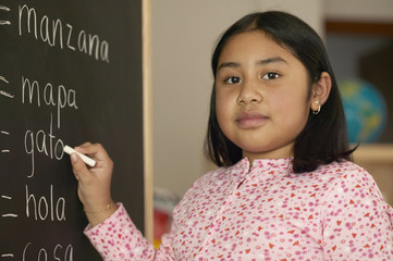 Portrait of girl writing on chalkboard