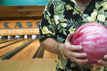Midsection of man holding ball at bowling alley