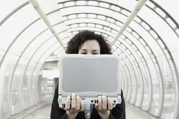 Businesswoman holding laptop in front of face
