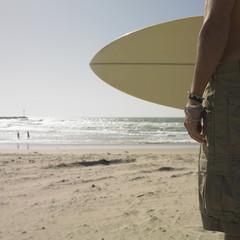 Man holding surf board at beach