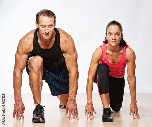 Athletic man and woman doing fitness exercise