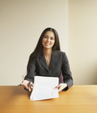 Businesswoman holding out a document to sign