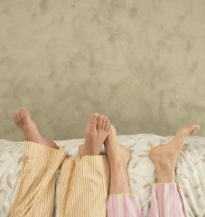 High angle view of couple's feet in bed