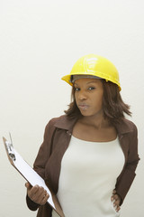 Woman wearing a hard-hat and holding clipboard