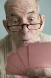 Elderly man holding a winning hand
