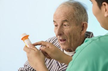 Nurse showing medication to elderly patient