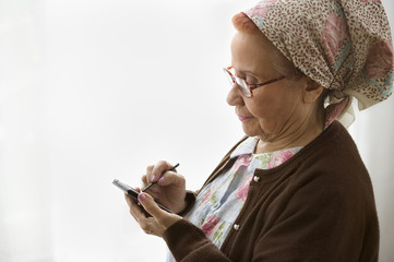 Profile of elderly woman using electronic organizer