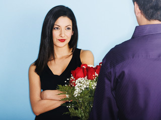 Young man giving skeptical girlfriend flowers