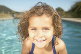 Young girl smiling next to swimming pool