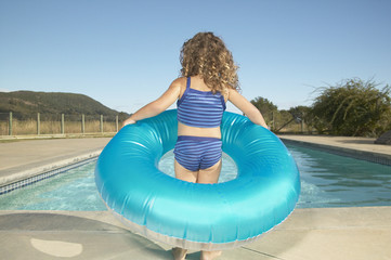 Young girl holding inner tube next to swimming pool