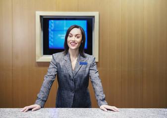 Businesswoman standing behind desk