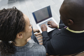 Two businesspeople outdoors sharing laptop