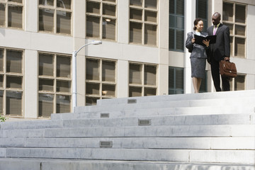 Two businesspeople talking on steps
