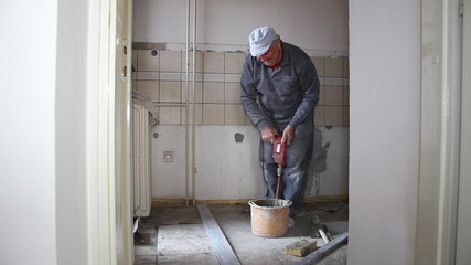 Senior man mixing adhesive for ceramic tiles