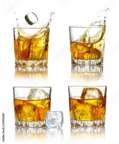 Set of scotch whiskey glasses with splash and ice isolated