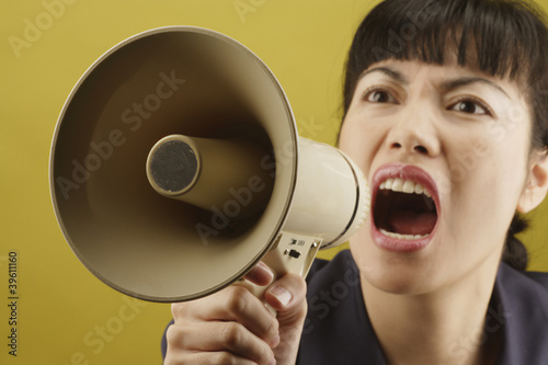 Asian businesswoman yelling into megaphone