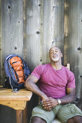 Middle-aged African American man resting in chair with backpack