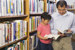 Father and daughter looking at library books