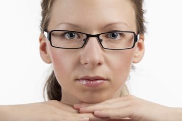 Auf Händen gestütztes Gesicht einer jungen Frau mit Brille