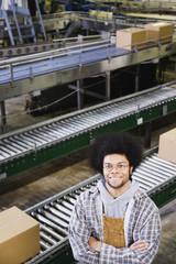 Workman standing in front of conveyor belt