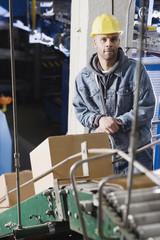 Man standing behind conveyor belt