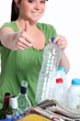 Young woman recycling plastic bottles