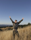 Elated man standing in field