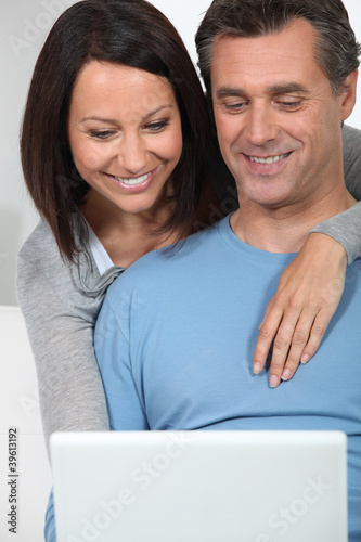 couple of fortysomethings looking happy with computer