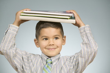 Boy balancing notebooks on his head
