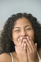 Teenage girl covering her mouth while laughing