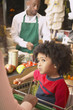 Young African American boy in shopping cart at supermarket checkout