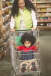 African American mother pushing young son in shopping cart