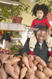 African American father with young son on shoulders in supermarket