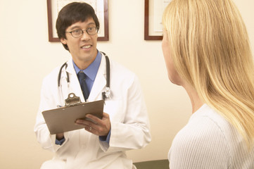 Asian male doctor with chart talking to patient