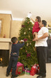Hispanic family decorating Christmas tree