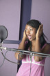 African American woman singing in recording studio