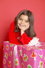 Hispanic girl leaning on large gift