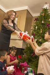 Hispanic woman giving son Christmas gift