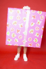 Child holding large gift with only legs showing
