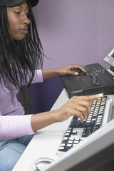 African American woman using computer and recording equipment