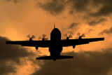 Lockheed C-130 Hercules turboprop cargo aircraft at sunset