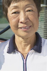 Close up of senior Asian woman with tennis racket