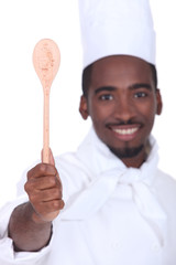 black cook showing a wooden spoon