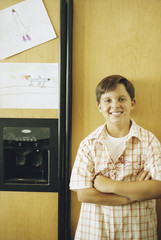 Young boy posing before refrigerator