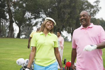 Two couples play golf together